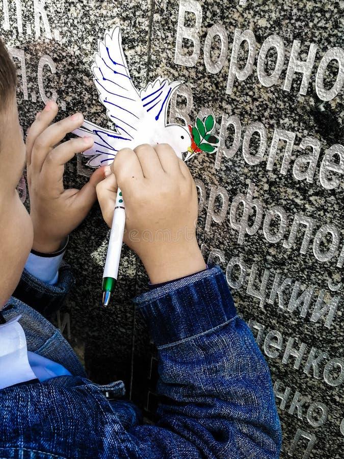 Lite skriver pojken på ett duvasnitt ut ur papper arkivbilder