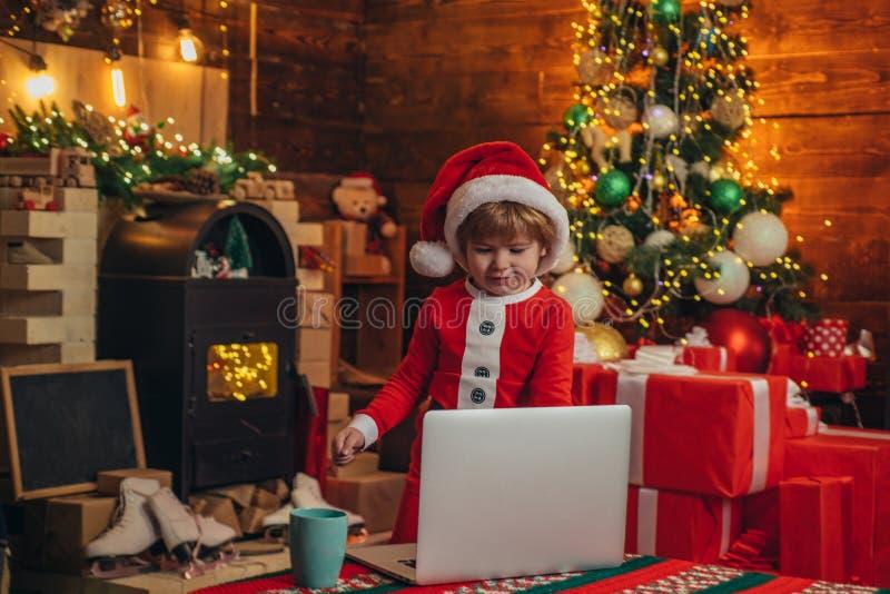 Lite snille E Pyssanta hatt och dr?kt som har gyckel Pojkebarn med bärbara datorn nära jul royaltyfria bilder