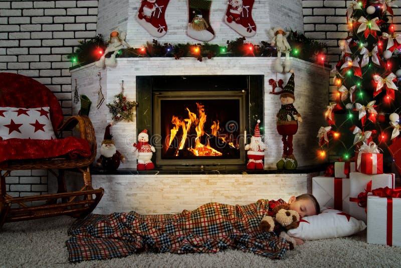 Lite sover pojken med en leksakhund under en julgran i ett rum med en brinnande spis royaltyfri fotografi