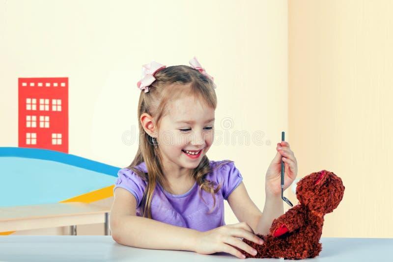 Lite spelar flickan doktorn - hon kontrollerar en leksakbjörn fotografering för bildbyråer