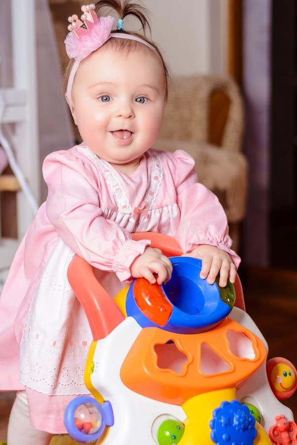 Lite spelar flickan i en rosa klänning en leksakbil nära lathunden arkivfoton