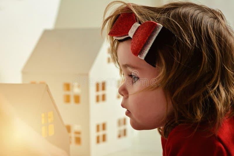 Lite spelar flickan med ett sagolikt litet leksakhus royaltyfri foto