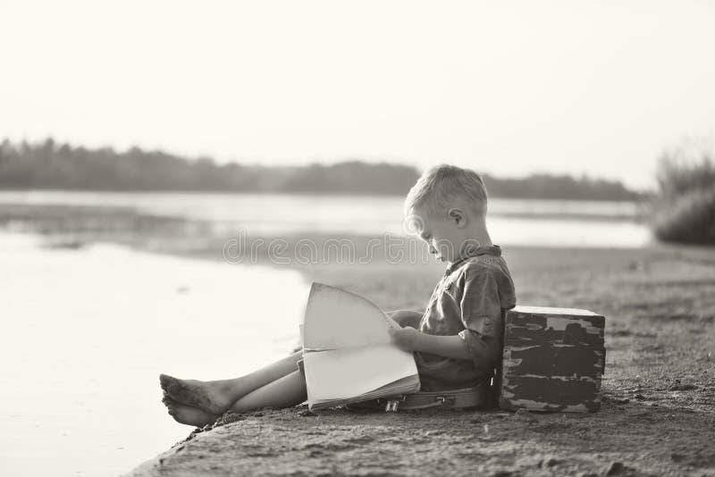 Lite spelar pojken på den sandiga flodbanken i sommar på solnedgången royaltyfri bild
