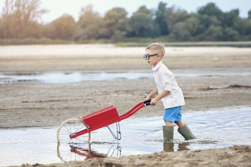 Lite spelar pojken på den sandiga flodbanken i sommar på solnedgången arkivbilder