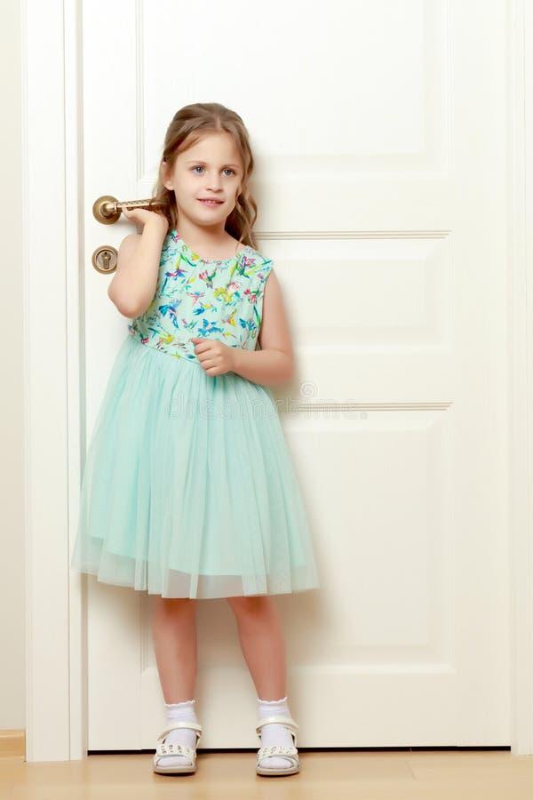 Lite står flickan vid dörren royaltyfria foton