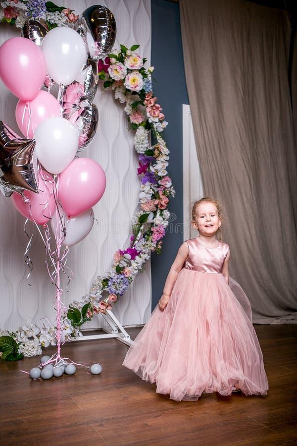 Lite står prinsessan i en härlig rosa färgklänning bredvid ballonger och en blommabåge som rymmer en klänning med henne händer oc royaltyfri foto