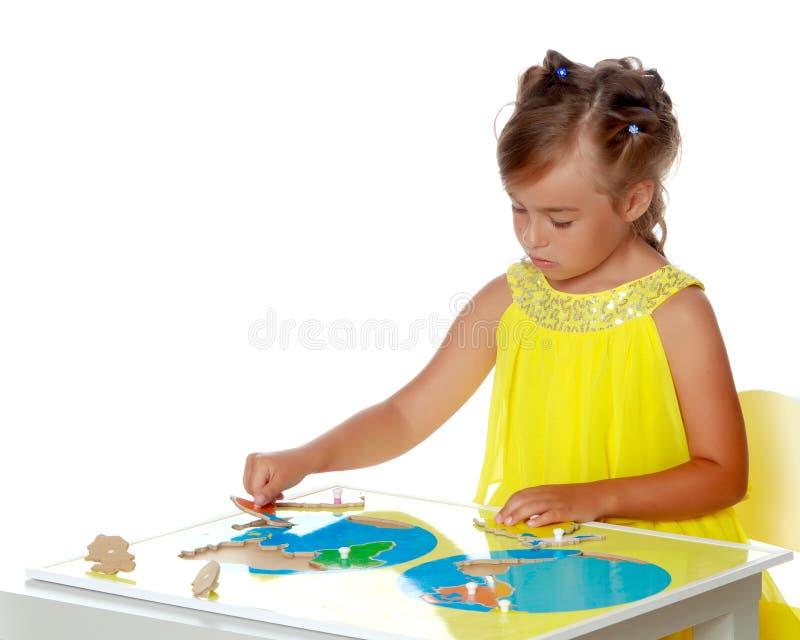Lite studerar flickan Montessori material royaltyfri fotografi