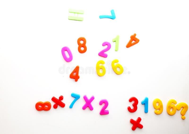Lite studerar pojken de magnetiska numren på kylen Förskolebarnutbildning arkivbilder