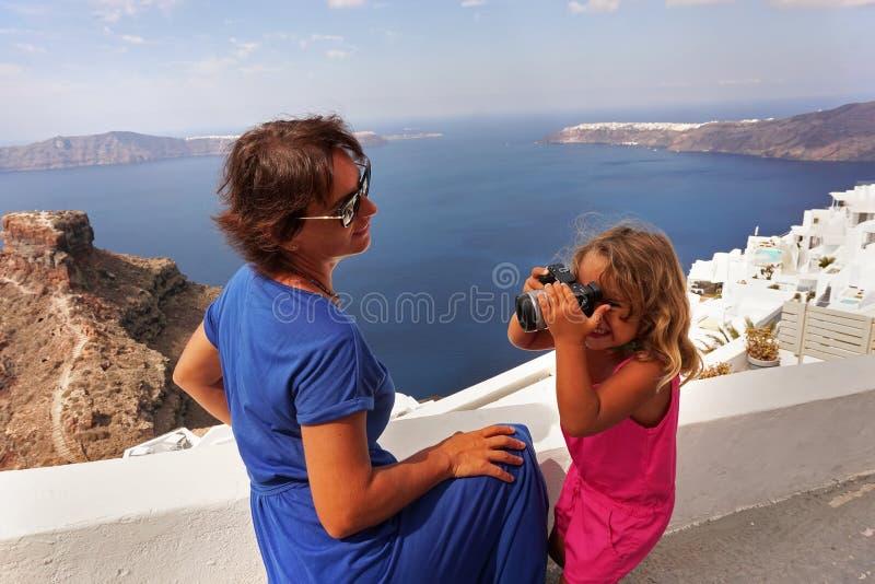lite tar flickan bilder av hennes moder mot den härliga havssikten av Santorini arkivfoto