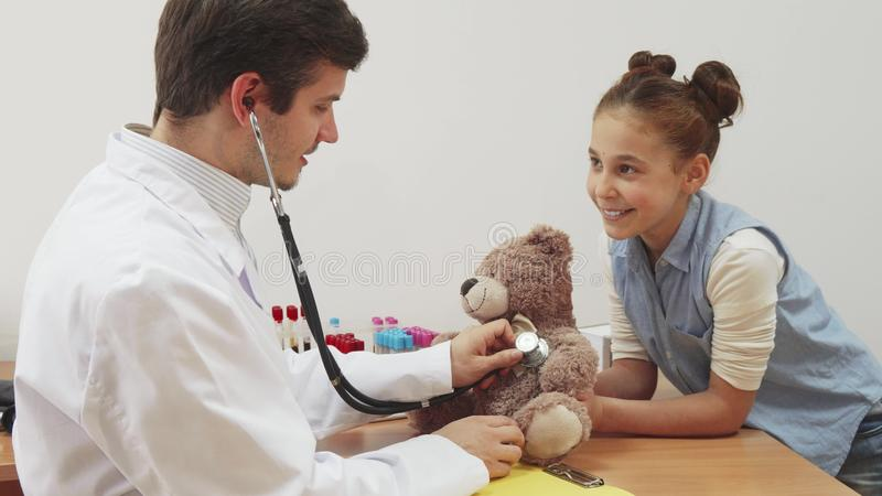 Lite tog flickan hennes nallebjörn till en tidsbeställning för doktors` s royaltyfria bilder