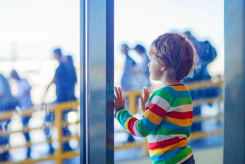 Lite trött ungepojke på flygplatsen som reser royaltyfri fotografi