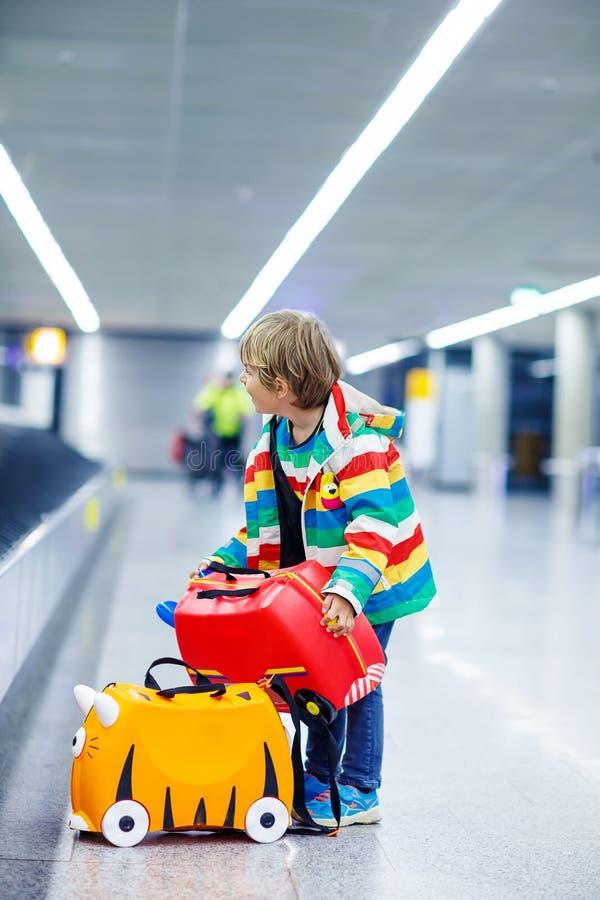 Lite trött ungepojke på flygplatsen som reser royaltyfria bilder