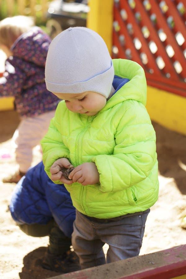 Lite två år gammal pojke som spelar lastbilleksaken i sandlåda, fyller på har han av sand hans spårvagnlastbil och gyckel på grun arkivbild