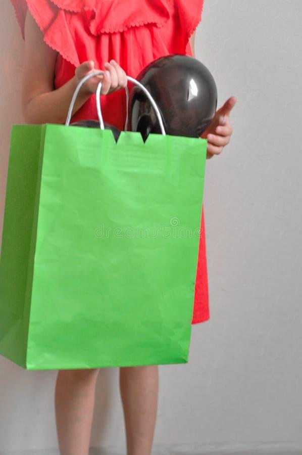Lite tycker om flickan med en packe i hennes hend att shoppa och försäljningen på en ljus bakgrund Barn i bra lynne fotografering för bildbyråer