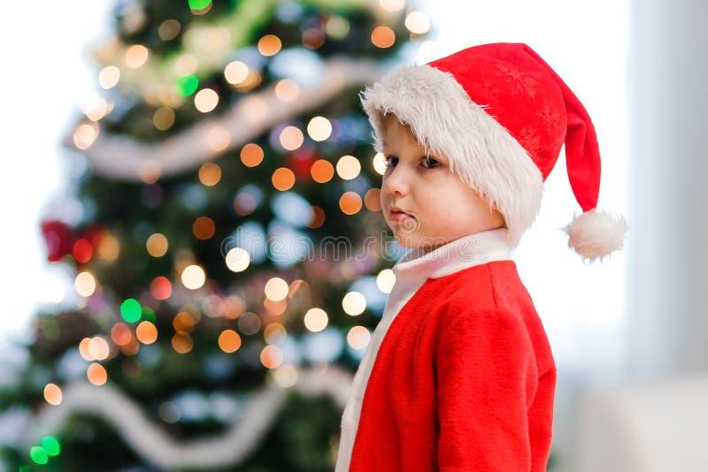 Lite unge i jultomtendräkt och en julhatt arkivfoto