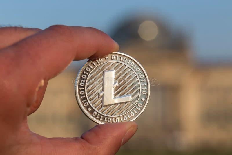 Litecoin在德语联邦议会柏林前面的一只手上 库存图片