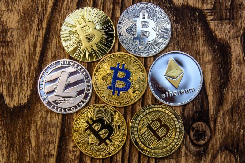 Litecoin, bitcoins en ethereum liggen op oude houten achtergrond stock foto's