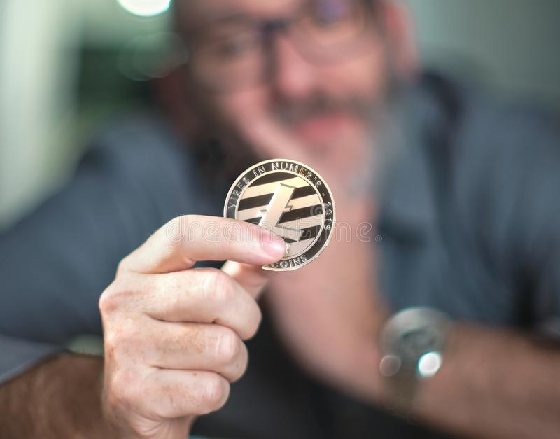Litecoin cryptocurrency在手中一个偶然商人 库存图片