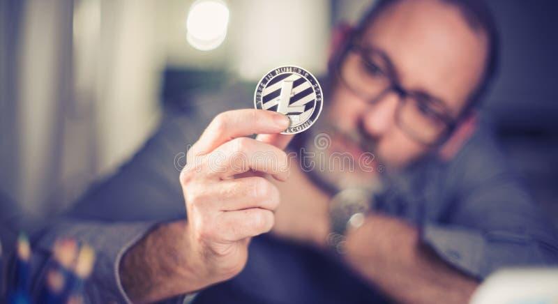 Litecoin cryptocurrency在手中一个偶然商人 库存照片