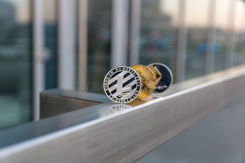 Litecoin d'argento e ethereum del bitcoin dorato sul corrimano del metallo fotografia stock libera da diritti