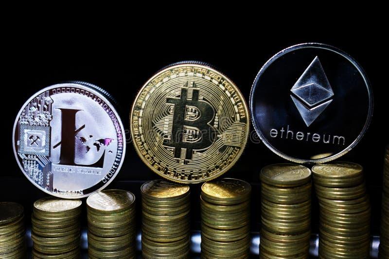 Litecoin fisico LTC, Bitcoin BTC e Ethereum ETH su un fondo scuro e sulle monete di oro fotografia stock libera da diritti