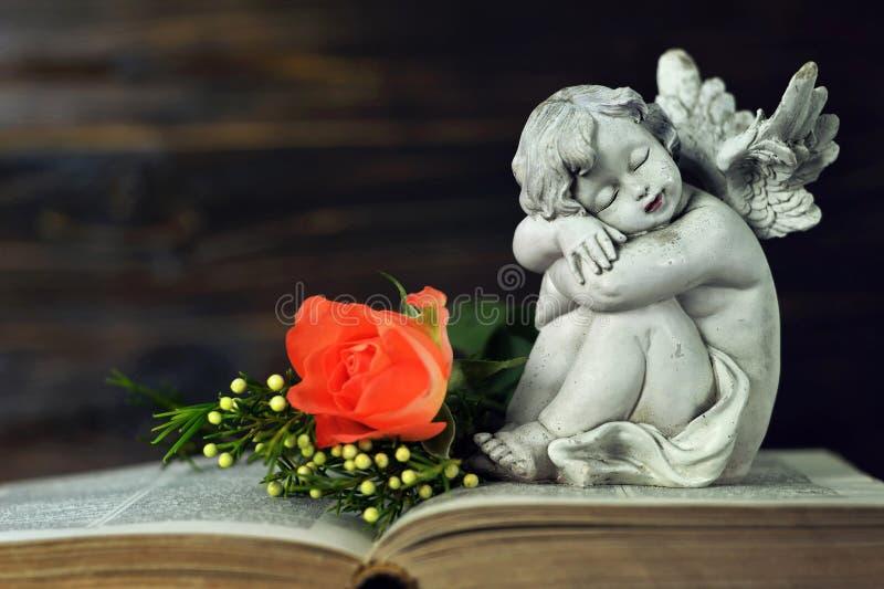 Liten ängel och blommor på boken arkivbild