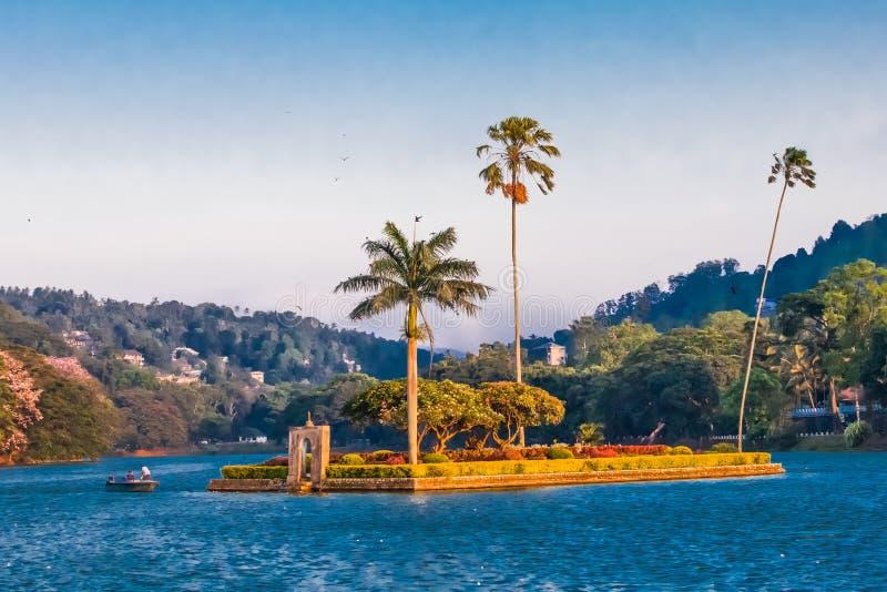 Liten ö med palmträd i mitt av Kandy sjön royaltyfria bilder