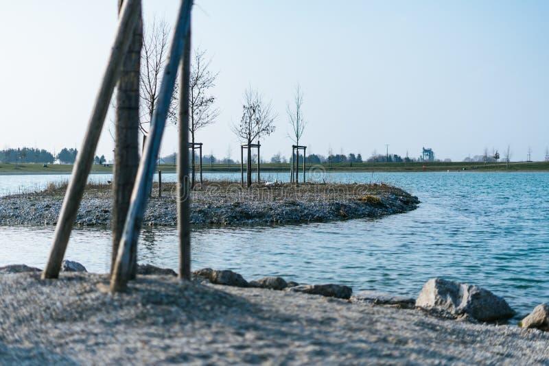 Liten ö på en sjö med träd royaltyfri fotografi