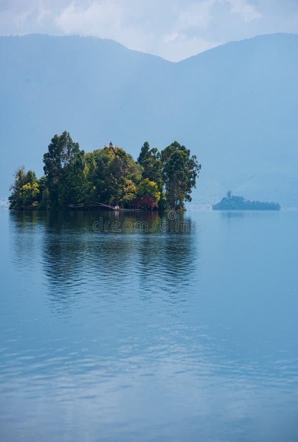 Liten ö som täckas med träd i Lugu sjön, Yunnan Sichuan, västra Kina royaltyfria bilder