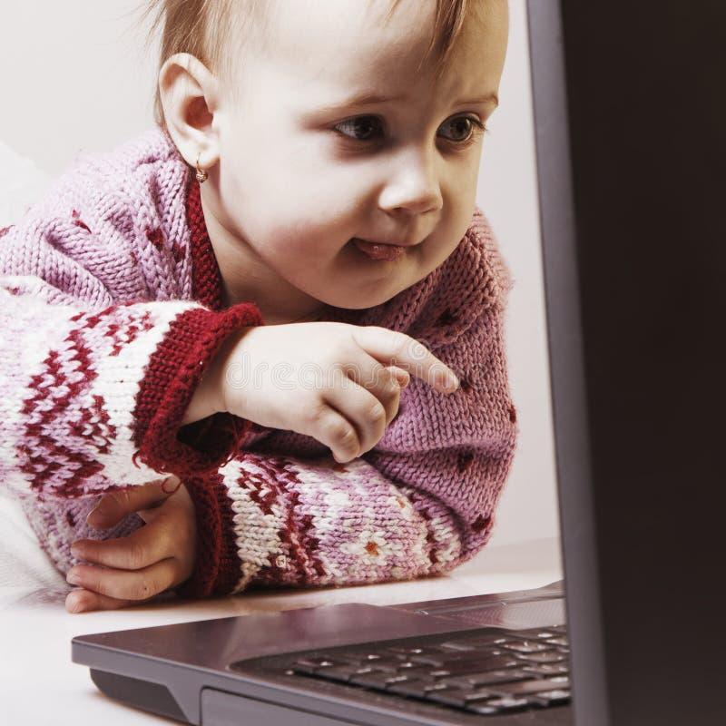 Liten affärsflicka som arbetar i ett kontor med en bärbar dator Humorou arkivfoton