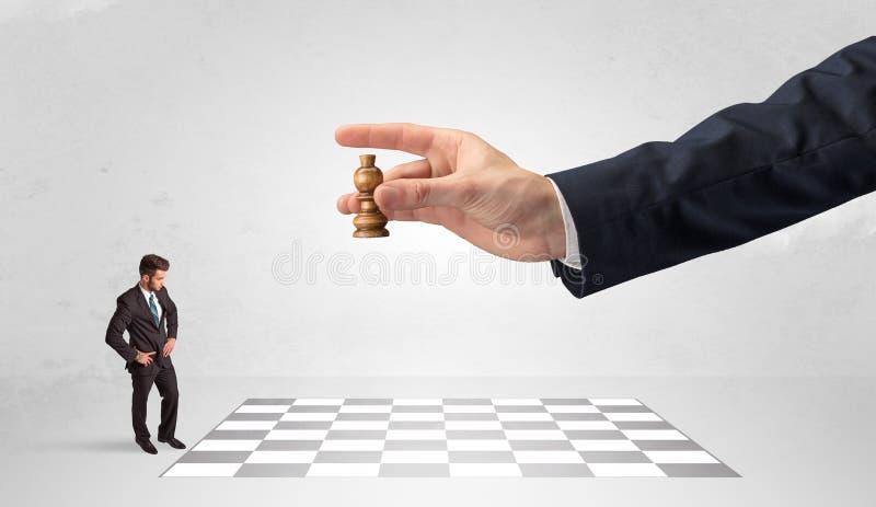 Liten aff?rsman som spelar schack med ett begrepp f?r stor hand fotografering för bildbyråer