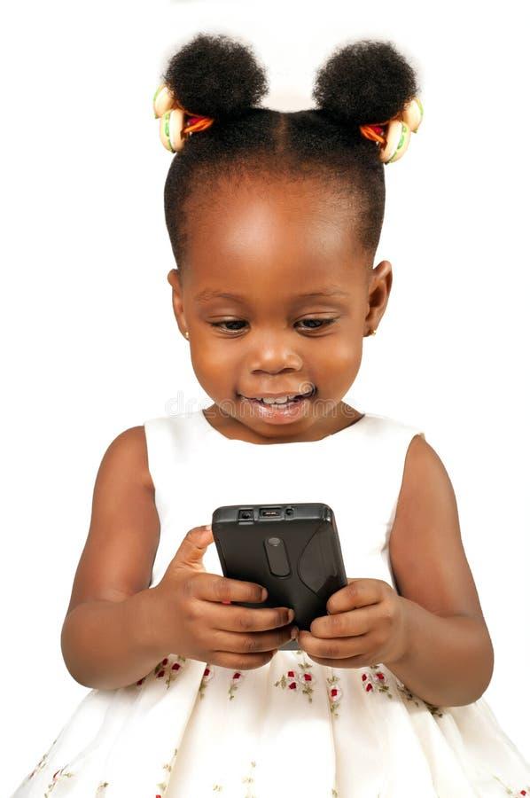 Liten afrikansk amerikanflicka med mobiltelefonen royaltyfria foton