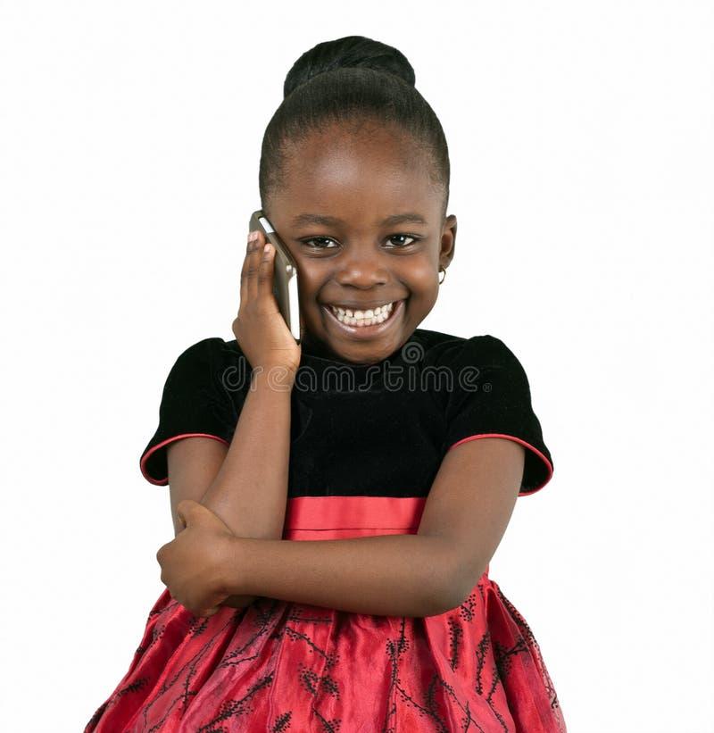 Liten afrikansk amerikanflicka som använder en mobiltelefon royaltyfri fotografi
