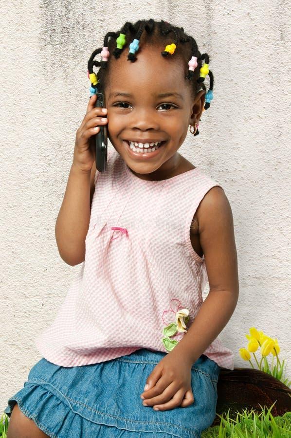 Liten afrikansk amerikanflicka som använder en mobiltelefon arkivbild