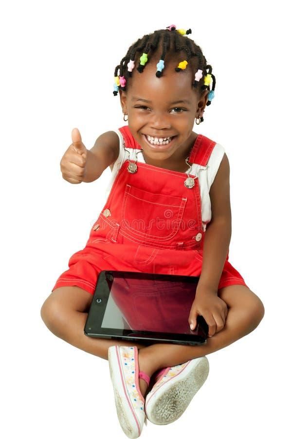 Liten afrikansk amerikanflicka som använder minnestavlaPC fotografering för bildbyråer