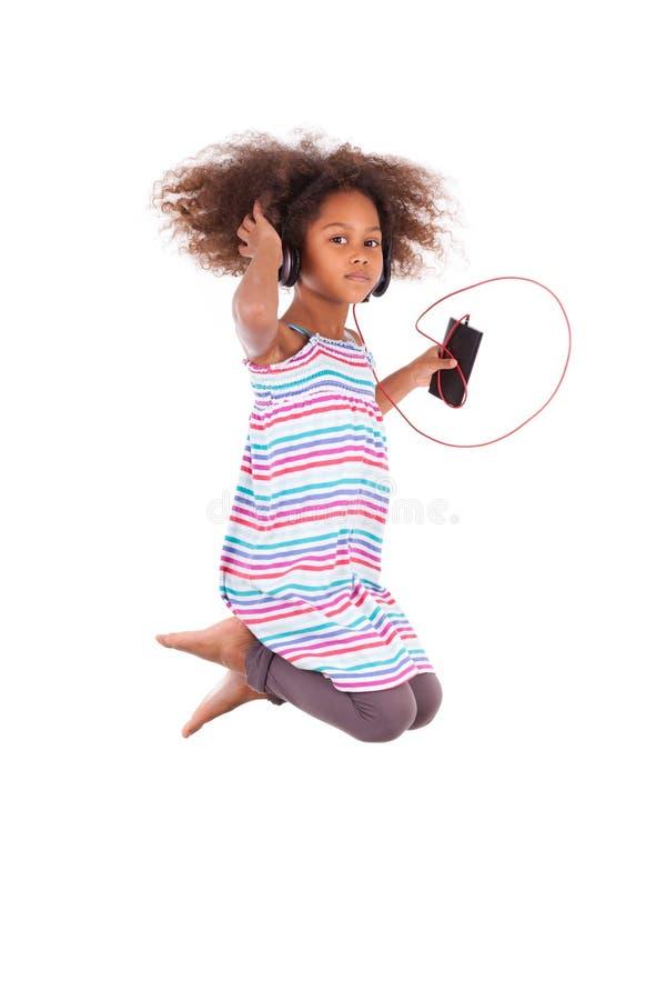 Liten afrikansk amerikanflicka som hoppar och lyssnar till musik - Bl royaltyfri foto