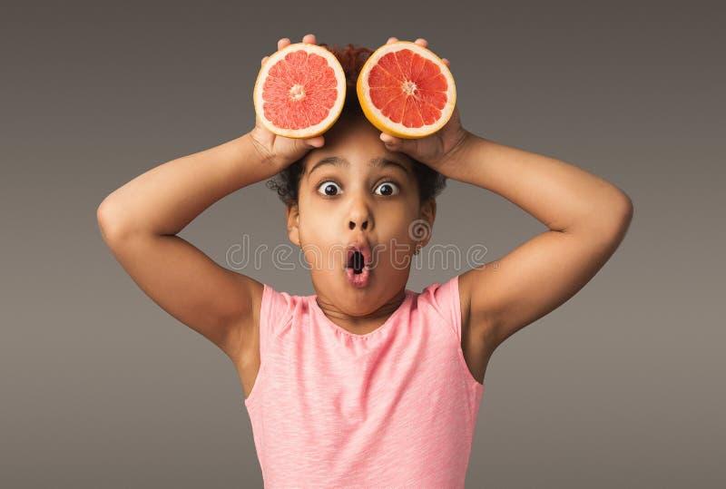 Liten afrikansk amerikanflicka som spelar med nya citrusfrukter fotografering för bildbyråer