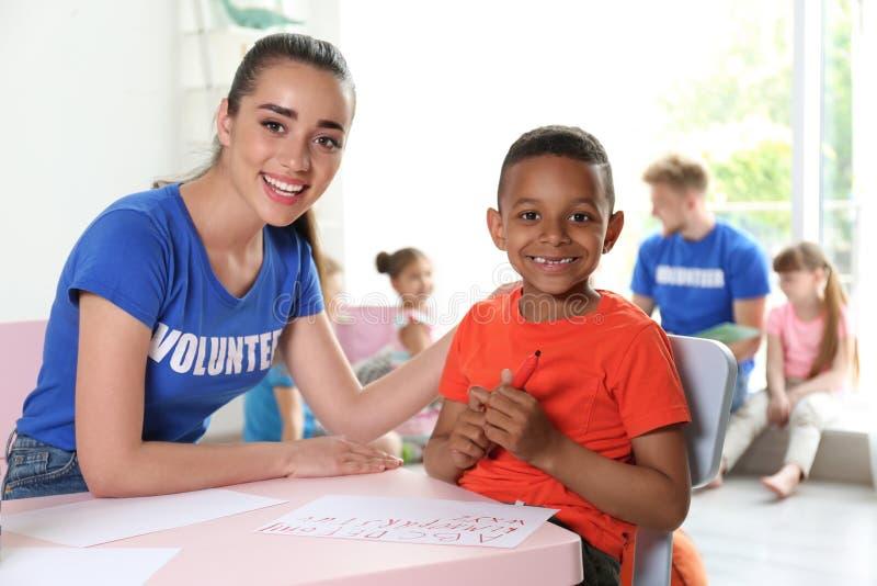 Liten afrikansk amerikanpojke som inomhus lär med volontären på tabellen royaltyfri bild