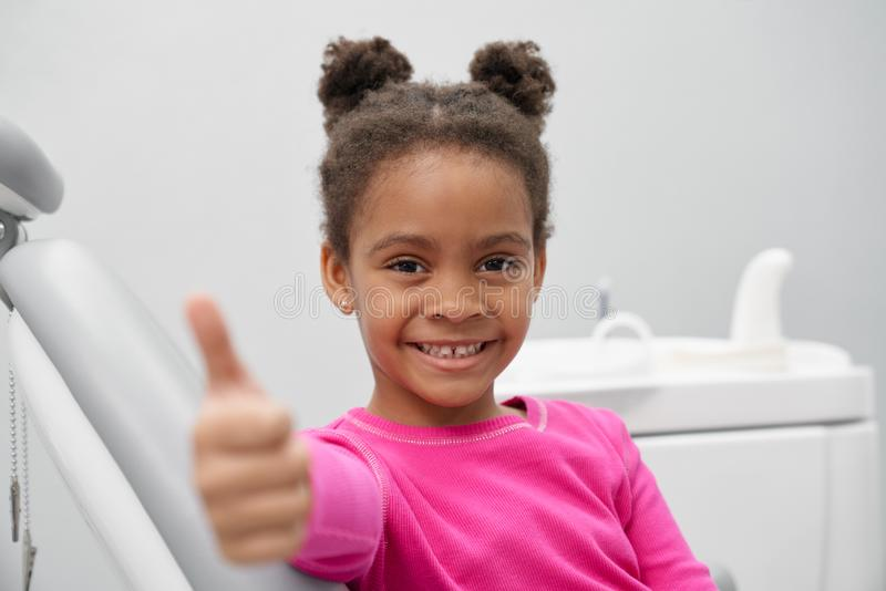 Liten afrikansk flickavisningtumme upp i tandläkarekontor arkivfoton