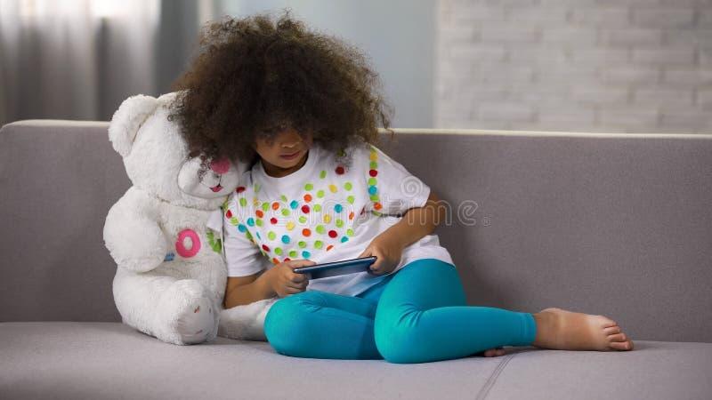 Liten afro--amerikan flicka som sitter på soffan och spelar leken på telefonen, böjelse royaltyfria bilder