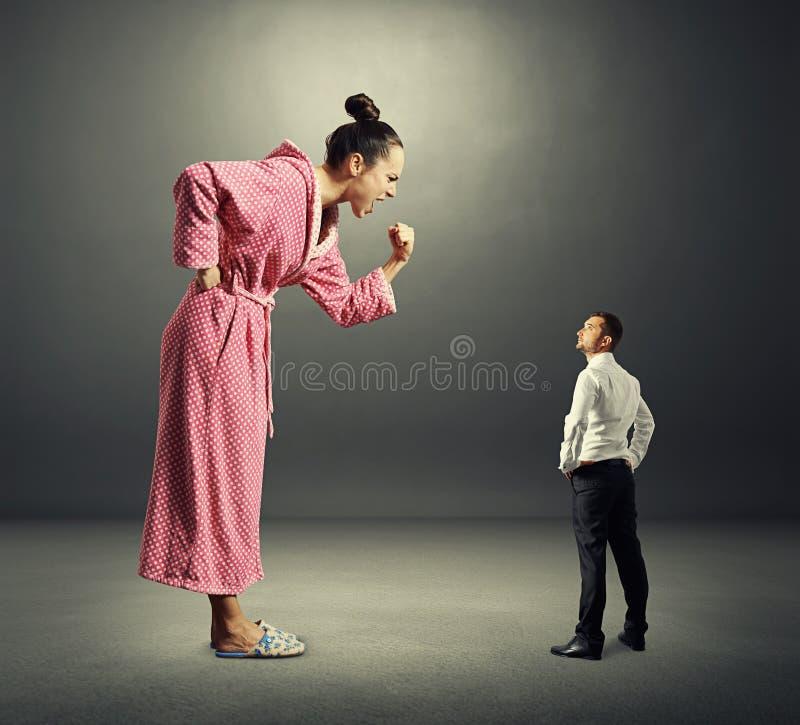Liten allvarlig man och stor ilsken kvinna royaltyfri bild