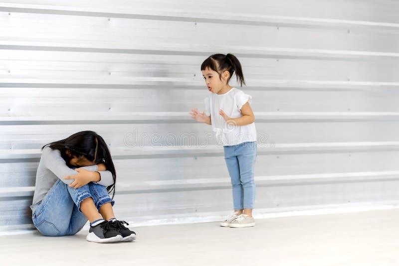 Liten asiatisk flickaåtlöje på äldre asiatisk flicka, som sitter och lågt ens huvud på golvet, vit vägg bak dem royaltyfri fotografi