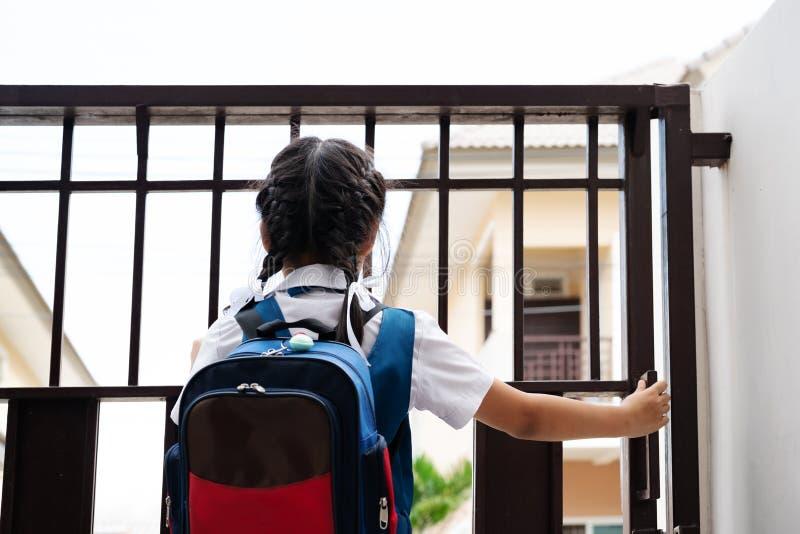 Liten asiatisk flicka i likformign som öppnar dörren för att lämna till skolan i morgonen med packen för blått tillbaka - arkivbilder