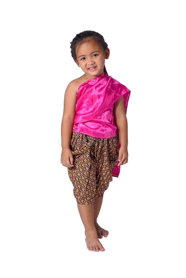 Liten asiatisk flicka i thai traditionella klänningar som isoleras på vit bakgrund arkivbild