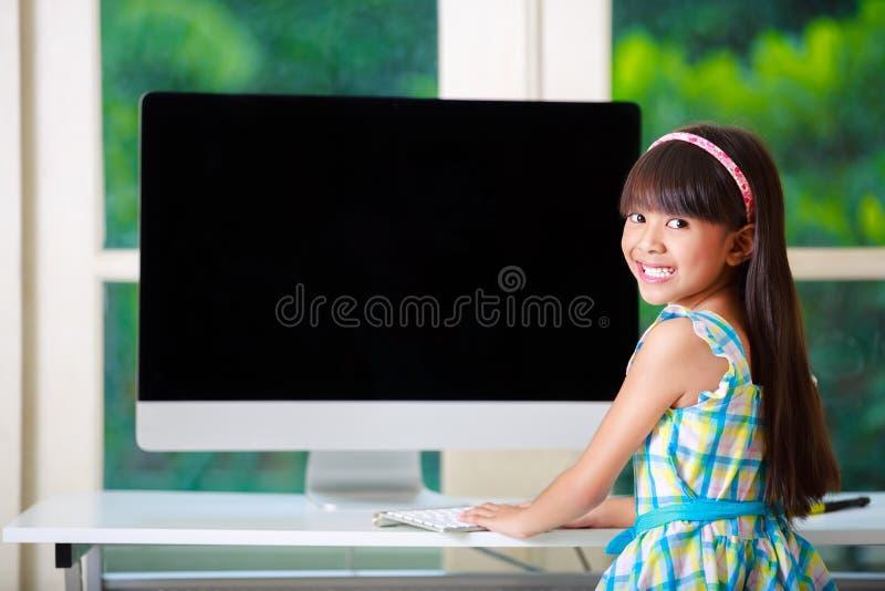 Liten asiatisk flicka med datoren arkivbilder
