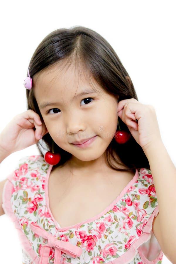 Liten asiatisk flicka med den nya röda körsbäret royaltyfri bild