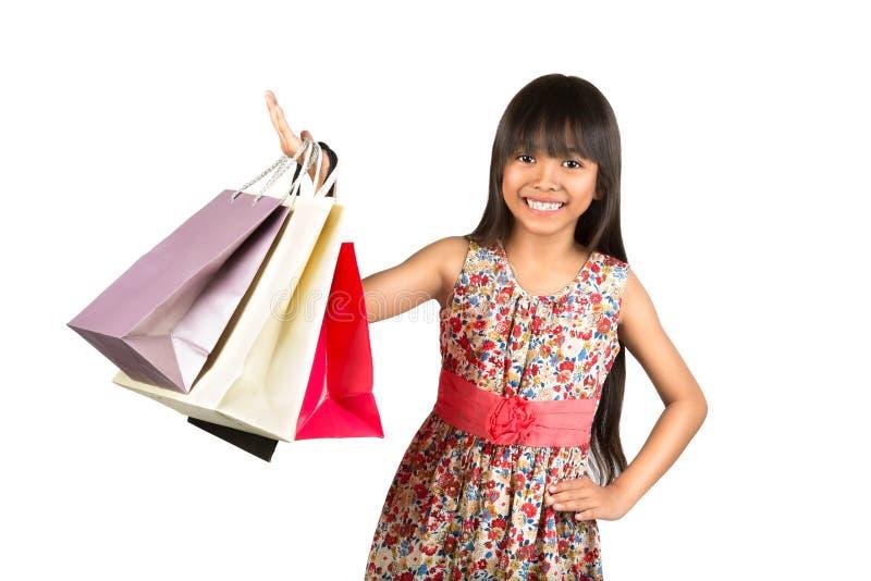 Liten asiatisk flicka med färgrika shoppingpåsar arkivfoto