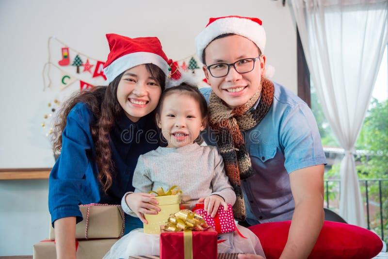 Liten asiatisk flicka och henne föräldrar med julgåvaaskar royaltyfria bilder