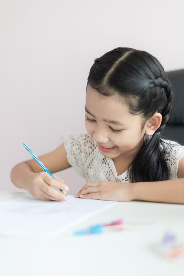 Liten asiatisk flicka som använder blyertspennan för att skriva på papperet som gör läxa och leende med lycka för det valda utbil arkivfoton
