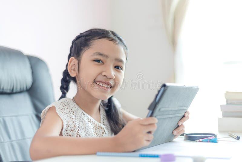 Liten asiatisk flicka som använder minnestavlan och leende med lycka för djup för vald fokus för utbildningsbegrepp grunt av fält royaltyfri bild